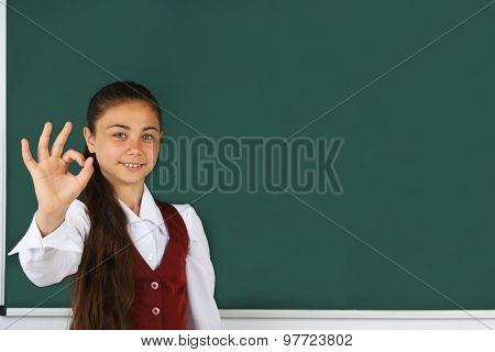 Beautiful little girl standing near blackboard in classroom