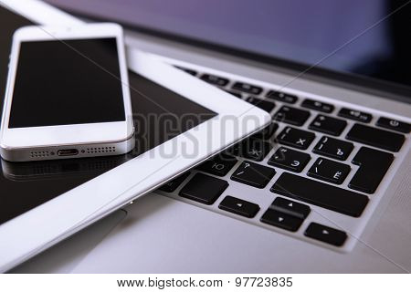 Tablet and mobile phone on keyboard, closeup