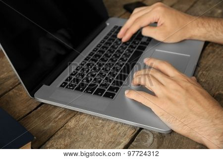 Man working on laptop on wooden table close up