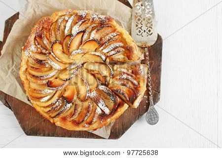 Homemade apple pie on cutting board on white wooden table background background