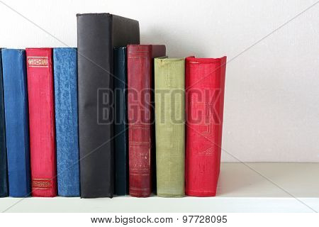 Old books on shelf, close-up, on light wall background