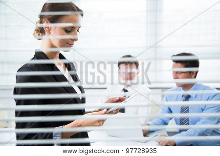 Businesswoman with tablet computer. View through blinds