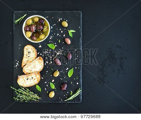 Mediterranean olives with herbs and ciabatta slices on black slate tray over dark grunge background,