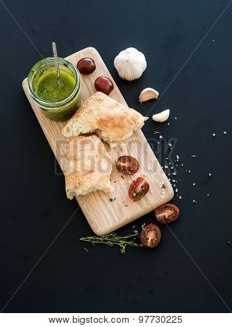 Pesto sauce in jar, ciabatta bread, cherry-tometoes, thyme and garlic on rustic wooden board over bl
