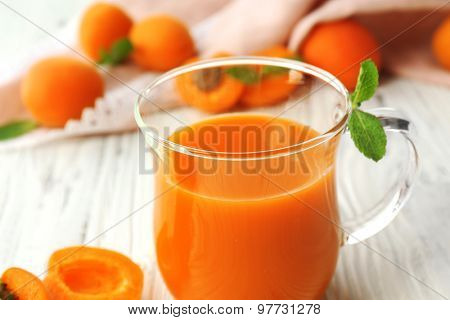Cup of apricot juice and fresh fruits on table close up