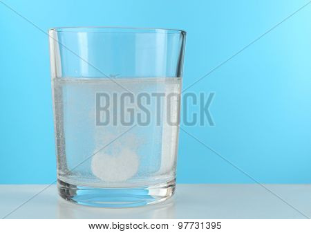 Pill in glass of water on blue background