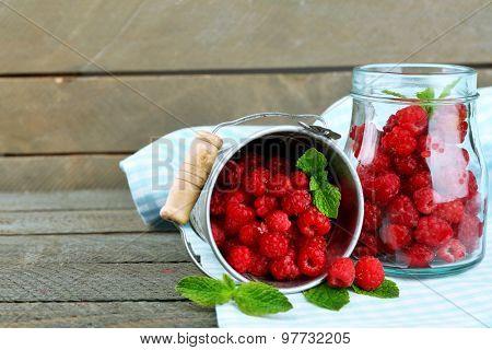 Sweet raspberries in decorative bucket on wooden  background