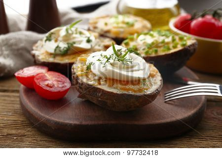 Baked potato with mayonnaise and herbs on wooden cutting board, closeup