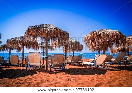 Straw Umbrellas And Sunbeds On A Sandy Beach In Greece