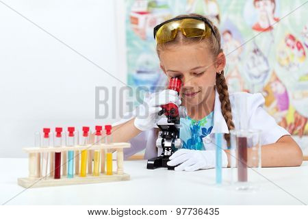 Little girl in elementary school science class using microscope