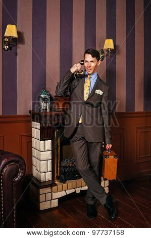 Businessman Talking On The Phone, Holding A Suitcase.