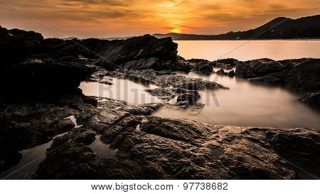 Colourful Orange Sunset Captured With Rocks In The Foreground By A Long Exposure Shot