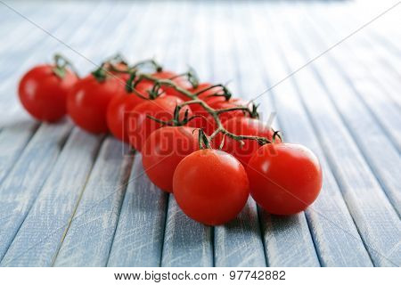 Fresh cherry tomatoes on wooden table close up