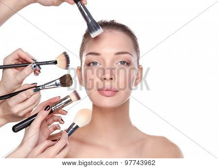 Closeup portrait picture of beautiful woman with brushes.