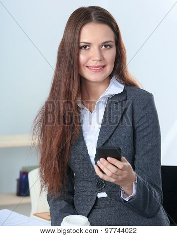Businesswoman sending message with smartphone sitting .