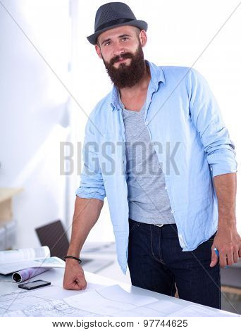 Portrait of male designer with blueprints at desk in office.