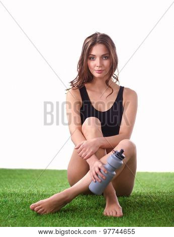 Young female athlete sitting on a grass after exericise and holding a water bottle.