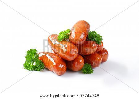stack of pan fried sausages on white background