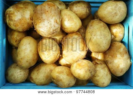 New potatoes in wooden crate, closeup