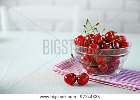 Cherries in glass bowl on table, on light background