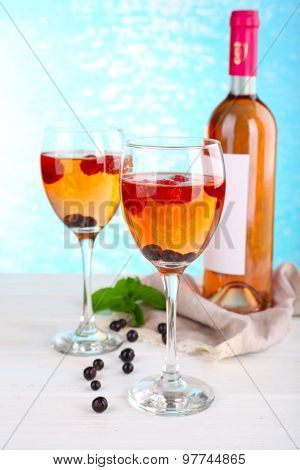 Glasses of wine with berries on light blurred background