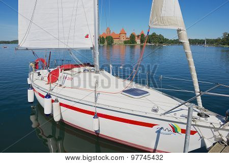 Sailboat tied at the Galve lake with Trakai castle at the background in Trakai, Lithuania.