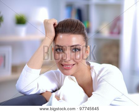 Portrait of beautiful woman sitting on couch at her room