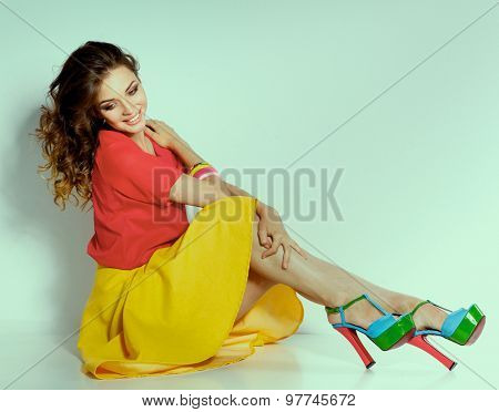 Young woman sitting on the floor, isolated in white background.