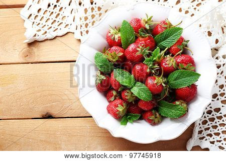 Red ripe strawberries in bowl, on color wooden background