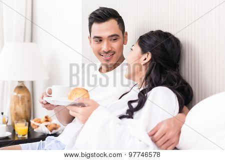 Asian couple lounging in bed at morning