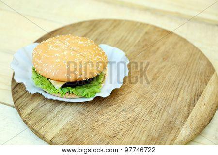 Tasty hamburger on wooden table close up
