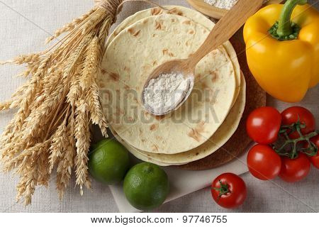 Stack of homemade whole wheat flour tortilla and vegetables on light background