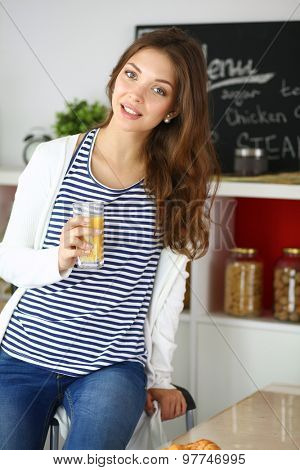 Portrait of a pretty woman holding glass with tasty juice .