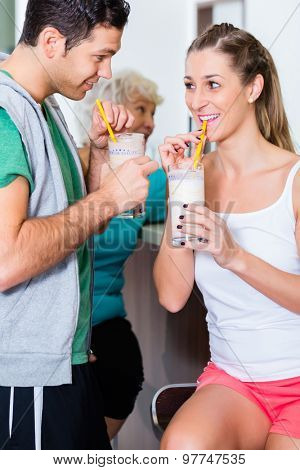 People drinking protein shakes in fitness gym bar