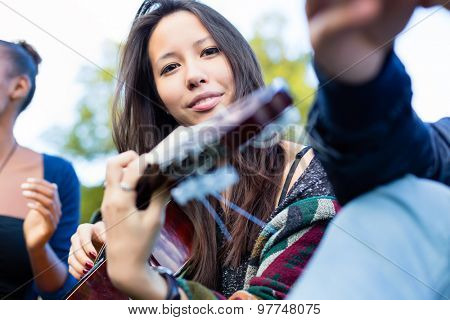 Guitar player Asian girl making music with friends in park
