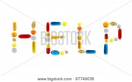 The word Help made with pills isolated on white