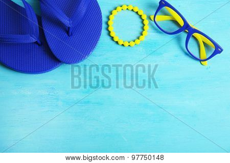 Flip flops, bracelet and glasses on wooden background