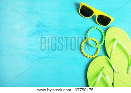 Flip flops, bracelets and sunglasses on wooden background