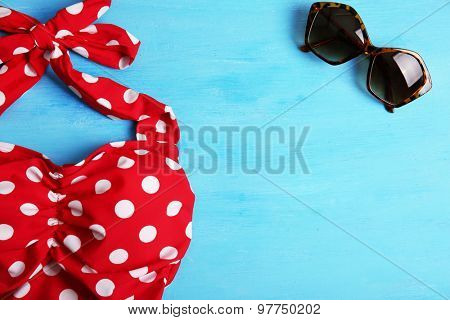 Swimsuit and sunglasses on wooden background