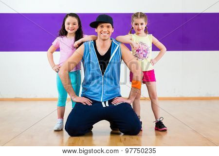 Young dancing teacher training children in modern zumba group choreography