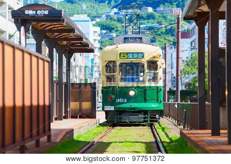 Green Public tram moving along the railway. Nagasaki city