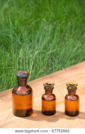 little brown bottles on booden board and green grass