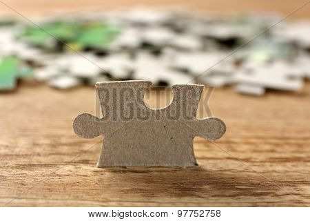 Puzzle pieces on wooden table, closeup
