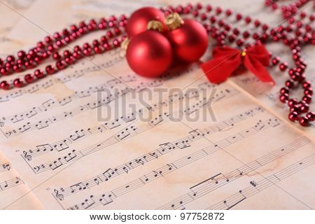 Christmas ball, beads and bow on music sheets background