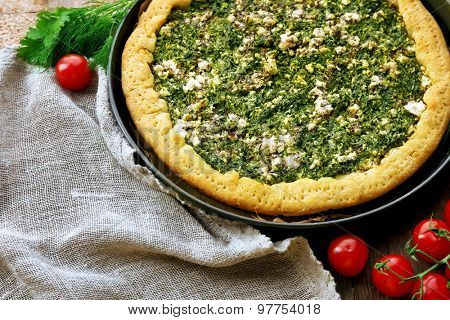 Open pie with spinach and tomato cherry on table close up