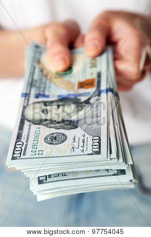 Female hands holding dollars, closeup