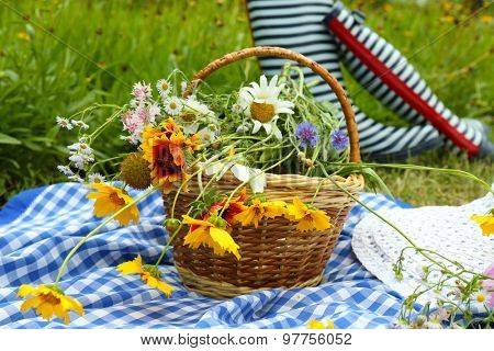 Beautiful composition with bouquet of wild flowers and rubber boots on meadow outdoors