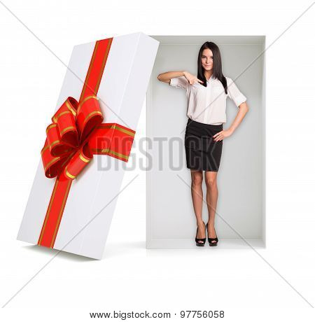 Businesslady looking at camera in gift box