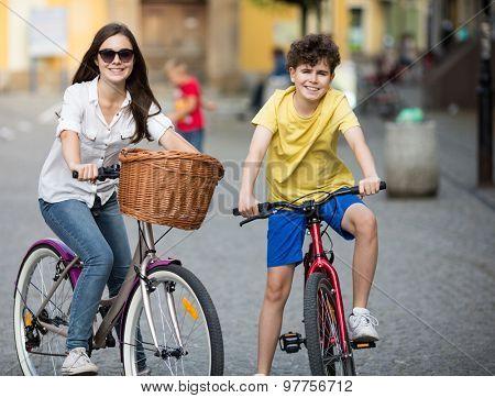 Urban biking - girl and boy riding bikes in city