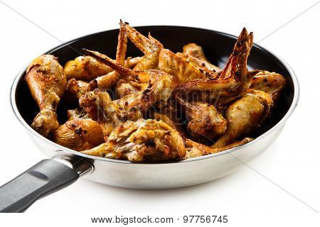 Fried chicken drumsticks and wings in frying pan on white background